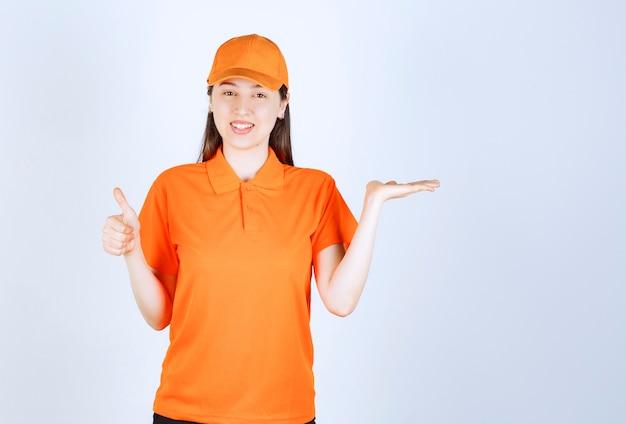 Vrouwelijke servicemedewerker die een oranje dresscode draagt en een positief handteken toont