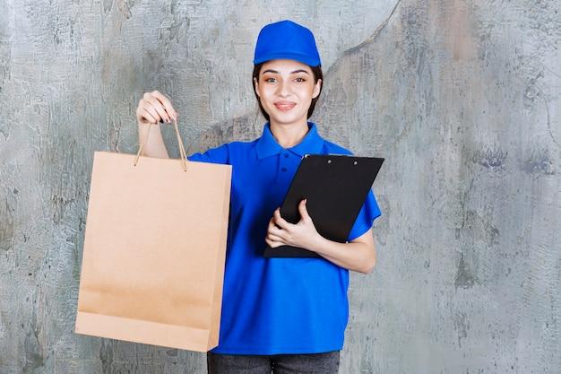 Vrouwelijke servicemedewerker in blauw uniform met een kartonnen boodschappentas en een zwarte klantenlijst