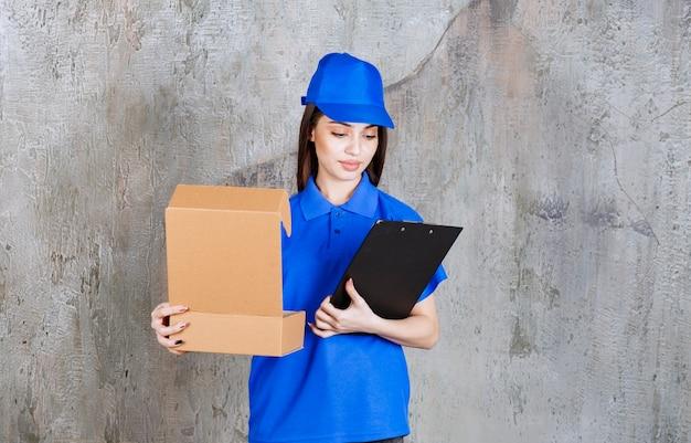 Vrouwelijke servicemedewerker in blauw uniform met een open kartonnen doos en een zwarte klantenmap