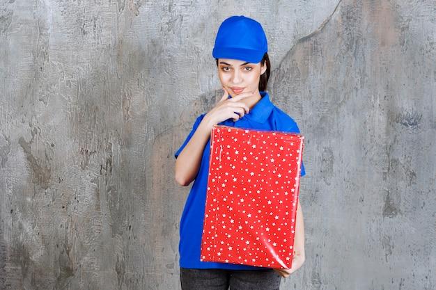 Vrouwelijke servicemedewerker in blauw uniform met een rode geschenkdoos met witte stippen erop en ziet er attent of dromerig uit.