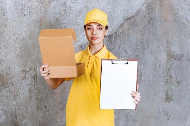 Vrouwelijke servicemedewerker in geel uniform die een open kartonnen doos vasthoudt en om een handtekening vraagt