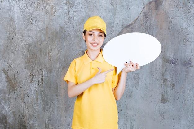 Vrouwelijke servicemedewerker in geel uniform met een ovaal infobord