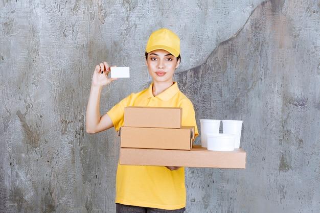 Vrouwelijke servicemedewerker in geel uniform met een voorraad afhaalkartonnen dozen en plastic bekers terwijl ze haar visitekaartje presenteert