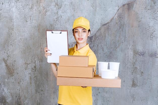 Vrouwelijke servicemedewerker in geel uniform met een voorraad kartonnen dozen en plastic bekers en vraagt om een handtekening.