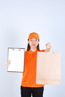 Vrouwelijke servicemedewerker in oranje dresscode die een kartonnen boodschappentas vasthoudt en de handtekeninglijst aan de klant presenteert