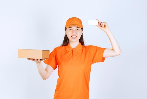 Vrouwelijke servicemedewerker in oranje dresscode die een kartonnen doos vasthoudt en haar visitekaartje presenteert