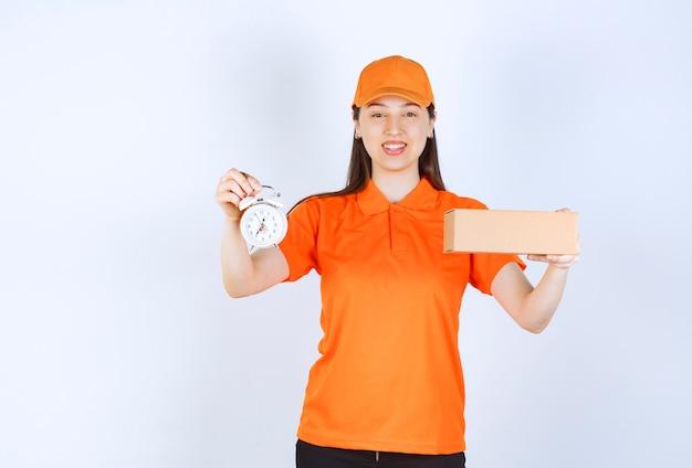 Vrouwelijke servicemedewerker in oranje dresscode met een kartonnen doos en een wekker