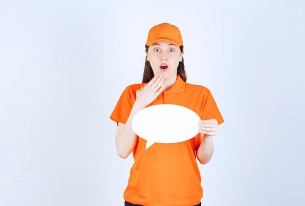 Vrouwelijke servicemedewerker in oranje dresscode met een ovaal infobord en kijkt verrast en doodsbang.