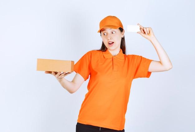 Vrouwelijke servicemedewerker in oranje kleur dresscode die een kartonnen doos vasthoudt en haar visitekaartje presenteert.