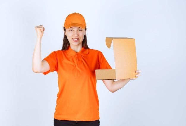 Vrouwelijke servicemedewerker in oranje kleur dresscode die een open kartonnen doos vasthoudt en een positief handteken toont