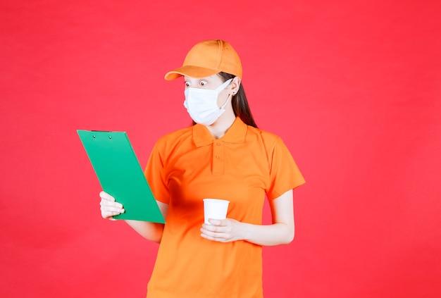 Vrouwelijke servicemedewerker in oranje kleur dresscode en masker die een nieuw merk wegwerpbeker presenteert en de details met emoties controleert.