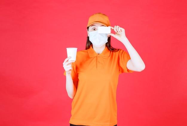 Vrouwelijke servicemedewerker in oranje kleur dresscode en masker die een wegwerpbeker vasthoudt en haar visitekaartje presenteert