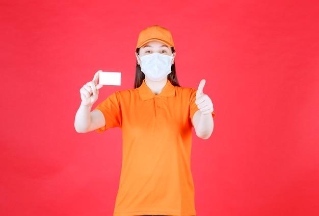 Vrouwelijke servicemedewerker in oranje kleur dresscode en masker die haar visitekaartje presenteert en een positief handteken toont