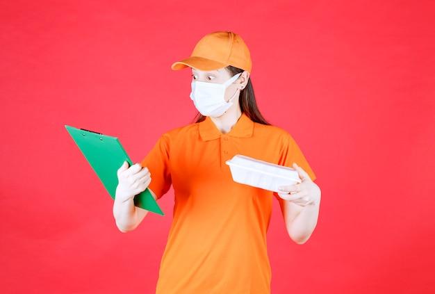Vrouwelijke servicemedewerker in oranje kleur dresscode en masker met een afhaalmaaltijdenpakket en het controleren van de groene map.