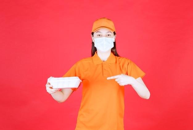 Vrouwelijke servicemedewerker in oranje kleur dresscode en masker met een afhaalmaaltijdenpakket