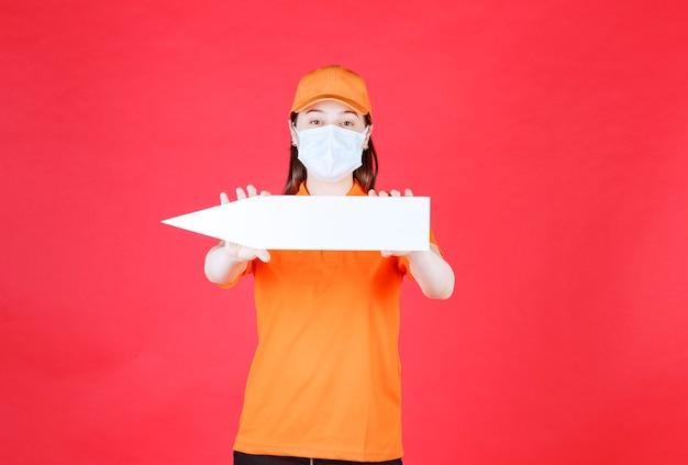 Vrouwelijke servicemedewerker in oranje kleur dresscode en masker met een pijl naar links.
