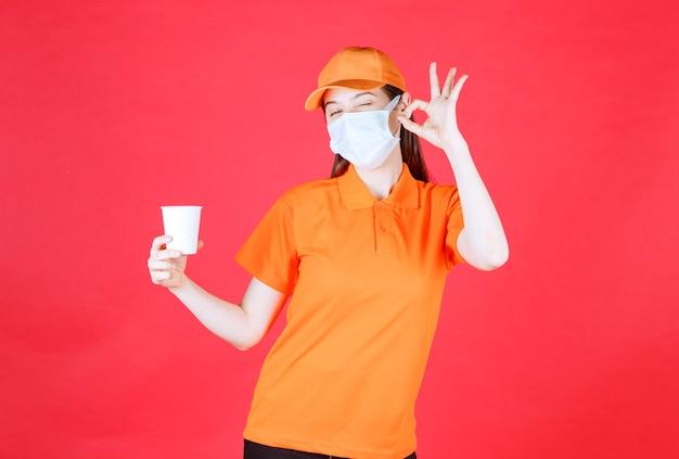 Vrouwelijke servicemedewerker in oranje kleur dresscode en masker met een wegwerpbeker en positief handteken