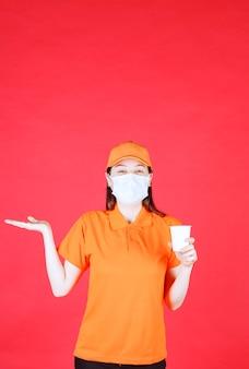 Vrouwelijke servicemedewerker in oranje kleur dresscode en masker met een wegwerpbeker