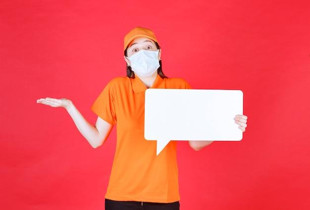 Vrouwelijke servicemedewerker in oranje kleur dresscode en masker met een wit rechthoekig infobord en ziet er verward en onzeker uit
