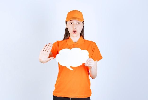 Vrouwelijke servicemedewerker in oranje kleur dresscode met een infobord in de vorm van een wolk en iets stoppen