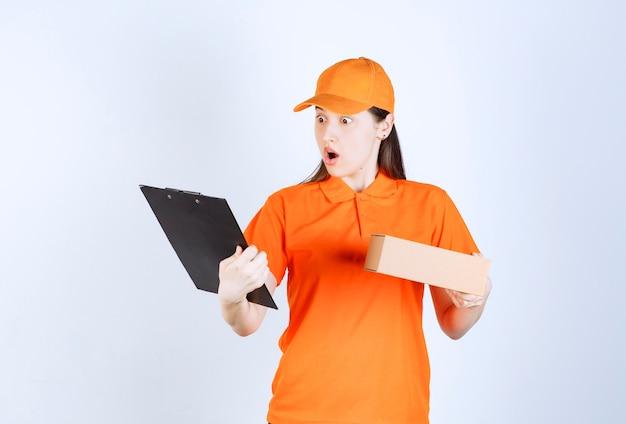 Vrouwelijke servicemedewerker in oranje kleur dresscode met een kartonnen doos, de klantenlijst lezend en wordt doodsbang