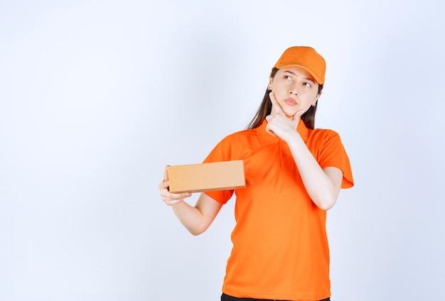 Vrouwelijke servicemedewerker in oranje kleur dresscode met een kartonnen doos, ziet er attent en dromend uit.