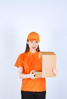 Vrouwelijke servicemedewerker in oranje kleur dresscode met een open kartonnen doos, kijkt naar binnen en wordt verrast