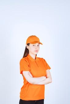 Vrouwelijke servicemedewerker met oranje dresscode, armen over elkaar en ziet er professioneel uit.