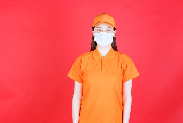 Vrouwelijke servicemedewerker met oranje dresscode en masker