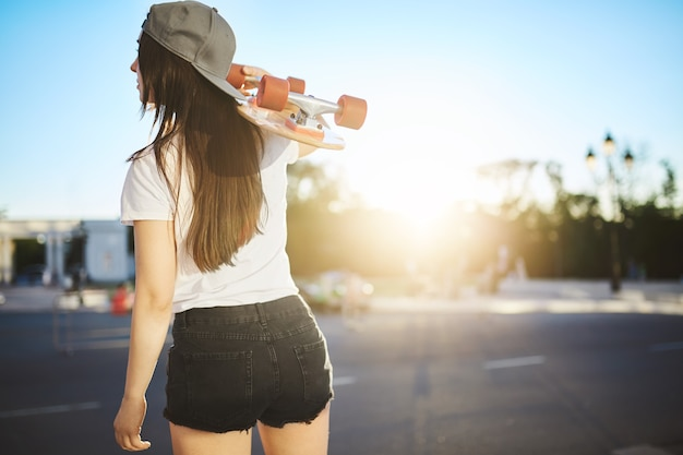 Vrouwelijke skateboarder houdt haar longboard in een zoektocht naar skate plek in een stedelijke omgeving op een zonnige zomerdag.