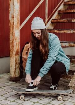 Vrouwelijke skater zit naast haar skateboarden buitenshuis