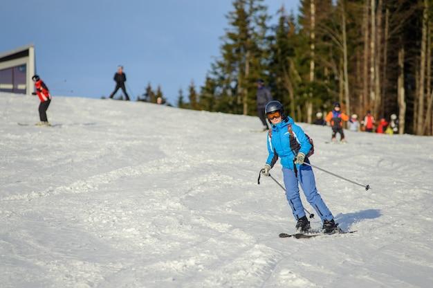 Vrouwelijke skiër die bergaf skiån ski? en