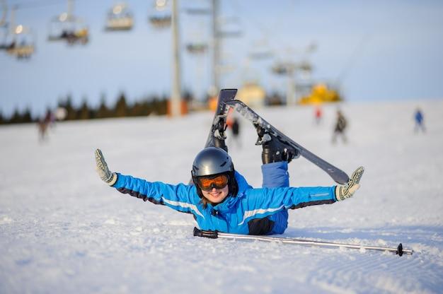 Vrouwelijke skiër die op de sneeuw ligt en pret heeft bij skitoevlucht