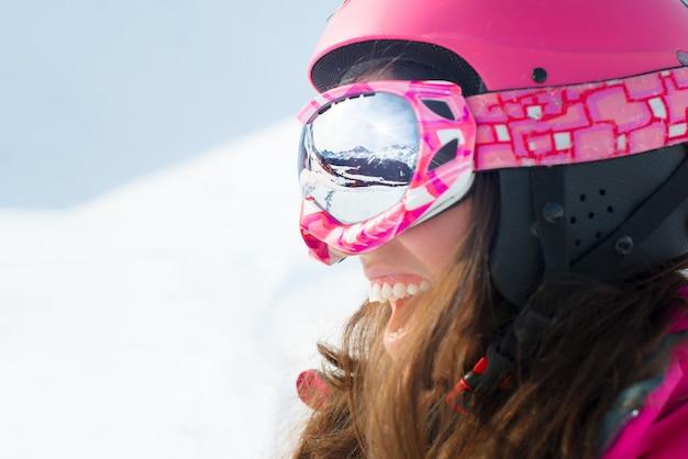Vrouwelijke skiër met ski's die en skiglazen glimlachen dragen