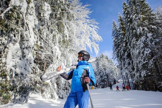 Vrouwelijke skiër op een skihelling in het de winterbos op een zonnige dag