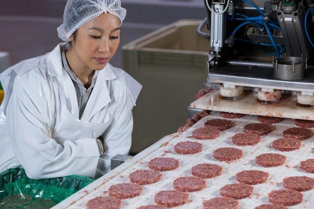 Vrouwelijke slager die hamburgerpasteitje verwerkt