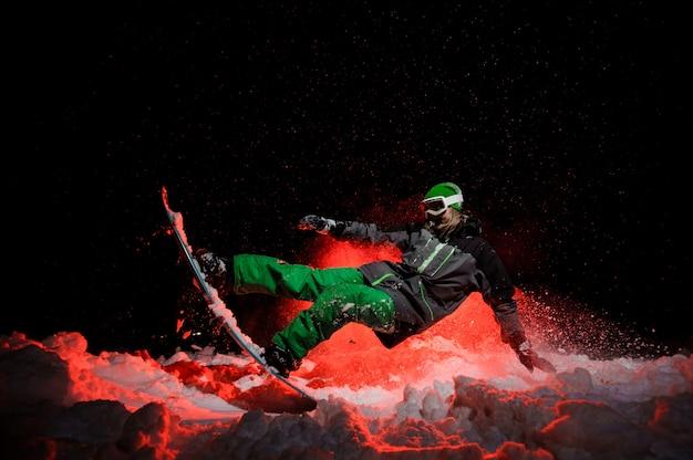 Vrouwelijke snowboarder gekleed in een groene sportkleding voert trucs op de berghelling uit