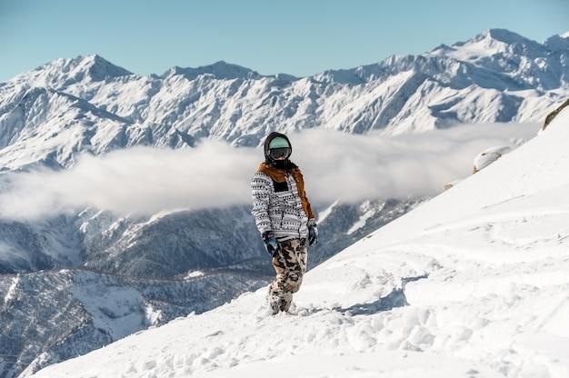 Vrouwelijke snowboarder in sportkleding die zich tegen de hoge bergpieken bevindt
