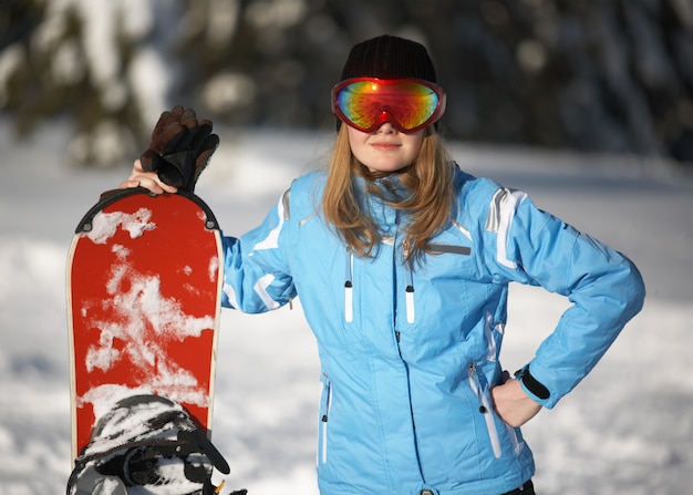 Vrouwelijke snowboarder op de winterachtergrond