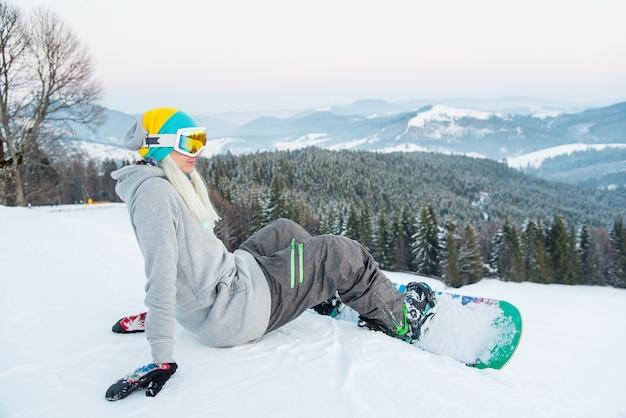Vrouwelijke snowboarder op helling in bergen