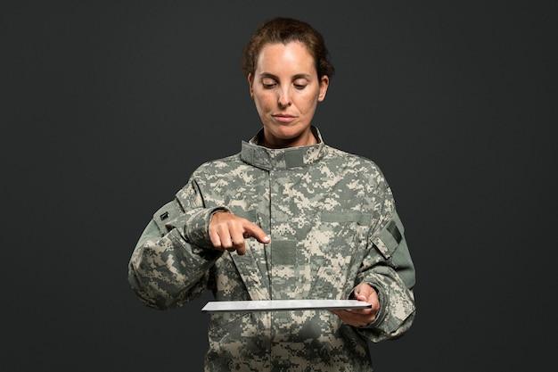 Vrouwelijke soldaat die wijsvinger op tablet drukt