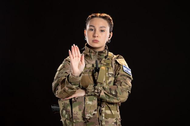Vrouwelijke soldaat in camouflage die gebaart om te stoppen op zwarte muur