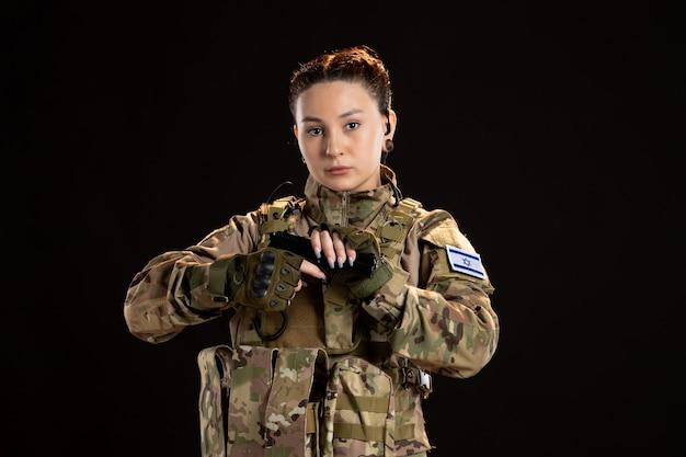 Vrouwelijke soldaat in camouflage gericht pistool op de zwarte muur