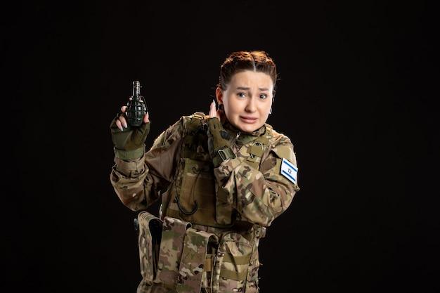 Vrouwelijke soldaat in camouflage met granaat in haar handen op zwarte muur