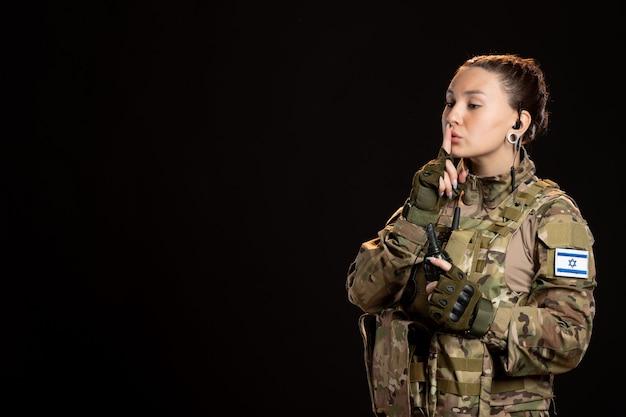 Vrouwelijke soldaat in camouflage met granaat op de zwarte muur