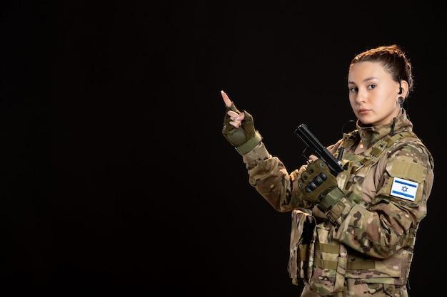 Vrouwelijke soldaat in camouflage met pistool op zwarte muur