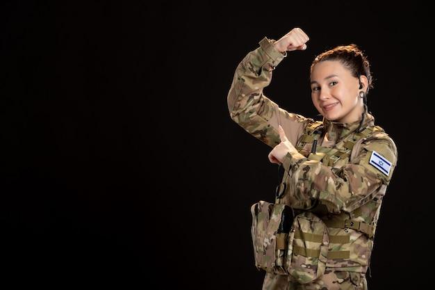 Vrouwelijke soldaat in camouflage op de zwarte muur