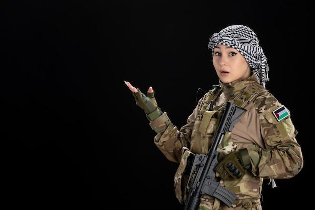 Vrouwelijke soldaat in militair uniform met geweer op zwarte muur