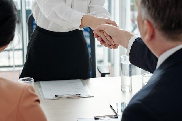 Vrouwelijke sollicitant schudt de handen van hr-manager en ceo van het bedrijf na succesvolle vergadering