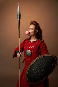 Vrouwelijke spartaanse krijger met schild en speer en kauwgom